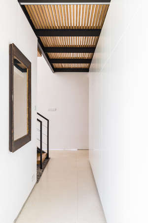 Narrow bright corridor with mirror and an openwork wooden ceiling