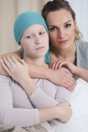 Portrait of friendly woman hugging sad girl with breast cancer wearing blue headscarf