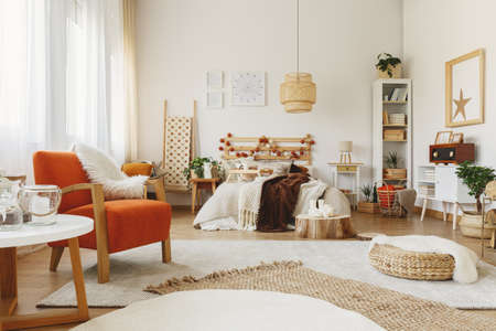 Fully furnished Scandinavian bedroom with a lot of rugs, chair, small table, and vintage radio Stock Photo