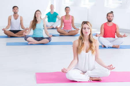 hombre flaco: Group of fit and young people meditating during yoga classes
