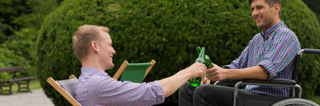 Smiling man on a wheelchair toasting beer with his friend in the park Stock Photo