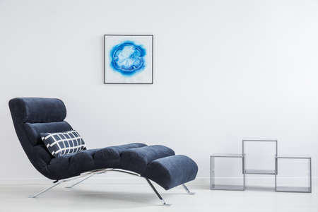 Bright psychologists office with navy blue settee, decorative shelves and abstract poster