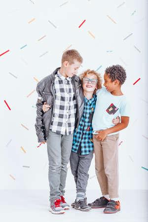 Muchacho de pelo rojo en gafas azules abrazando a sus dos amigos más bonitos Foto de archivo - 88219829