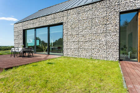Modern stone country house with terrace on a sunny day
