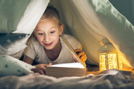 Young girl reading a book in the dark