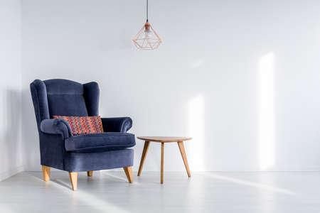 Koperen lampenkap opknoping boven donker blauwe fauteuil met kleurrijk kussen in de kamer met witte lege muur