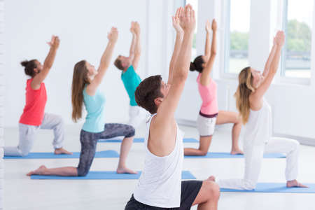 Yoga group performing a crescent long pose in a spacious gym room with large windows