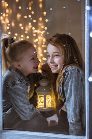 Two sisters sitting on the windowsill at night Stok Fotoğraf