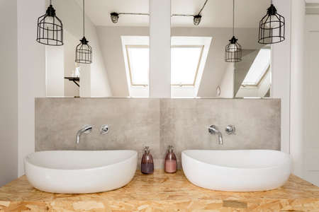Mirror and lamp above two bathroom washbasins in bright interior in the attic