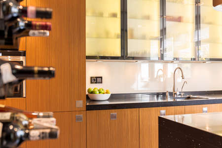 Modern kitchen with wooden door fronts and shelf with bottles of wine Stock fotó
