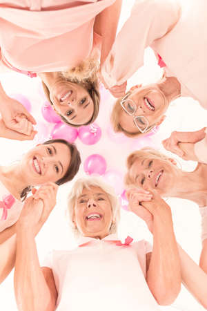fighting cancer: Medical, healthcare and breast cancer concept, women with pink ribbons united, supporting each other in cancer battle Stock Photo