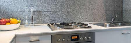 Partie de la cuisine avec un dessus de table blanc, une cuisinière en argent et un évier Banque d'images - 88232254