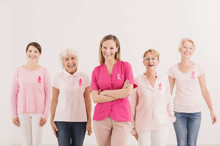 Concept of social breast cancer awareness campaign, five multigenerational women wearing pink ribbons smiling at camera
