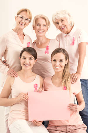 Copy space for breast cancer concept, group of happy women wearing breast cancer awareness pink ribbons and holding a banner