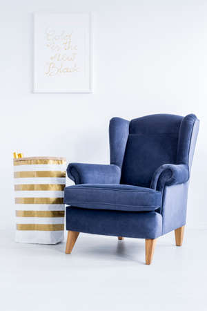 Striped material basket standing next to dark blue armchair in white room Imagens