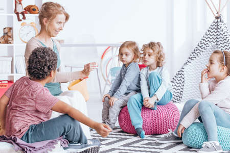 Multiculturele groep kinderen die woorden leren tijdens lessen met leraar op kleuterschool