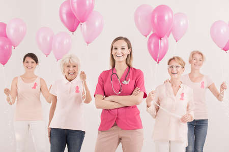 Medical concept, female oncologist and group of smiling breast cancer survivors with pink ribbons and balloons feeling happy