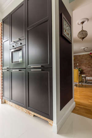Black kitchen cabinet with cooker in spacious apartment interior