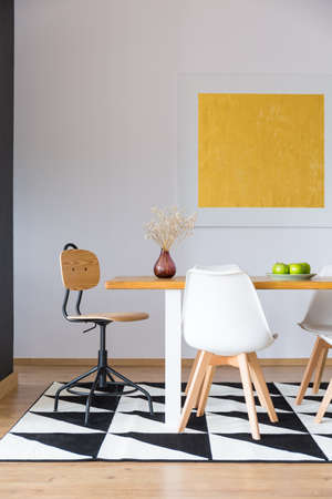 Yellow oil painting hanging over a wooden table standing on a large carpet in a flat interior Stock Photo