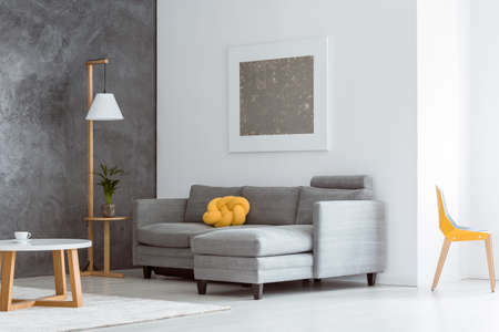 Canary yellow color accent in simple open living room interior with gray couch, modern wooden furniture and abstract painting on the white wall