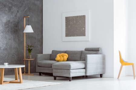 Sotaque de cor amarelo canário no interior de sala de estar aberto simples com sofá cinza, móveis de madeira modernos e pintura abstrata na parede branca