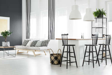 Braided basket next to kitchen island with bar stools in spacious living room with white sofa