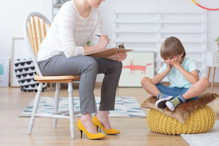 Children anxiety and depression concept, psychologist talking with sad little boy at the office Stock Photo