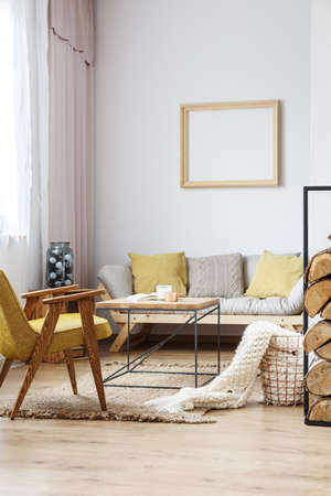 Apartment corner with beige sofa, mustard armchair and an end table in rustic style