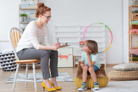 Friendly young child psychologist talking with little boy suffering from emotional disorder in bright office
