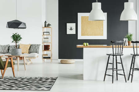 Goldmalerei auf schwarzer Wand im offenen Raum der skandinavischen Art mit Barhockern in Kücheninsel Standard-Bild - 88256220