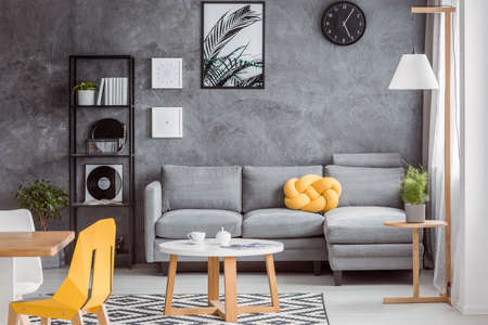Modern scandinavian decor in open space apartment with textured concrete wall, dining area, gray couch and yellow accessories