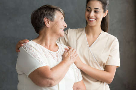 Satisfied caregiver supporting thankful elderly woman against dark background Stock Photo