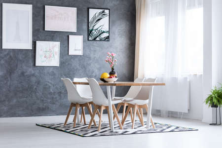 Pink flowers in decorative vase on table in dining room with gallery on textured dark wall
