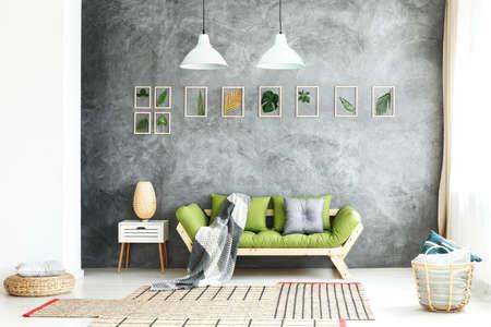Gebreide deken op houten bank, comfortabele poef en mand met zachte kussens in een gezellig woonkamerinterieur met natuurlijke groene accenten Stockfoto