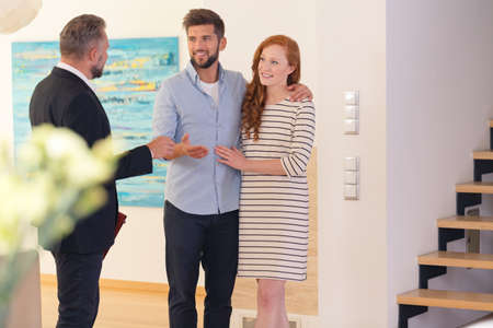 Engaged couple consulting with real estate agent while visiting a house for rent