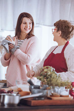 Young woman and grandmother smiling each other while standing in the kitchen Stock Photo