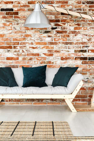 Accessories made of natural materials in trendy rustic apartment with jute rug, red brick wall and wooden sofa  Stock Photo