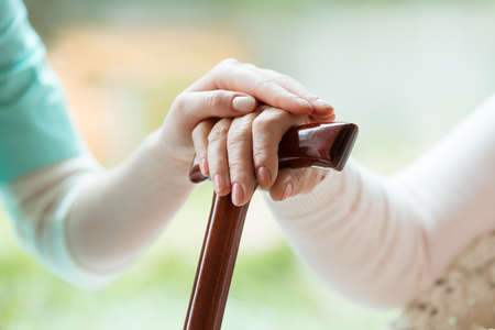 Senior holding hands on walking cane and nurse supporting her in nursing home Stockfoto
