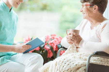 Smiling volunteer spending time with happy elder woman in a wheelchair with beige blanket Reklamní fotografie