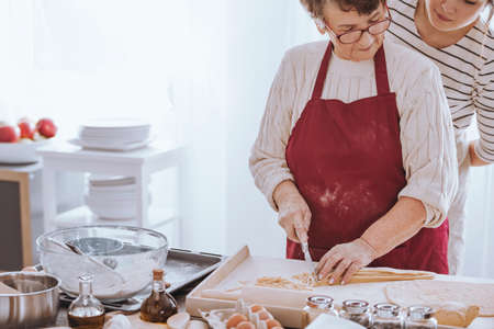 Grandmother in glasses concentrating on cutting dough and young woman watching her