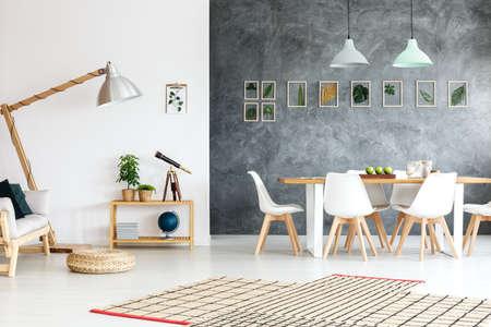 Interieur van modern appartement met houten sofa in witte woonkamer en open ruimte eetkamer met designer stoelen, gemeenschappelijke tafel en ingelijst planten