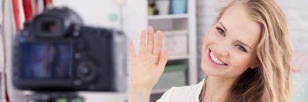 金髪女性ビデオブロガー録音エピソードの間に彼女のカメラに手を振って
