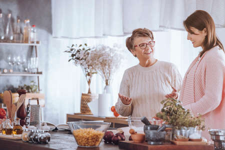 Happy grandmother talking with granddaughter while standing in the kitchen with ingredients on countertop Stockfoto