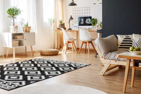 Black and white carpet and beige sofa in multifunctional living room with cozy work area