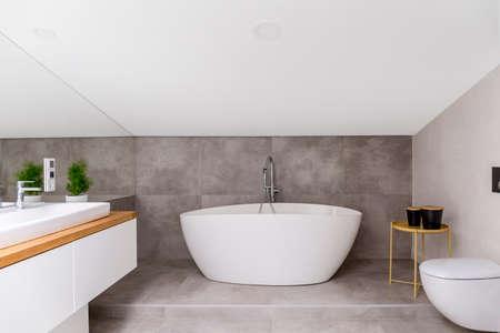 Houten kast en spiegel in eenvoudige grijze badkamer met ovale badkuip tegen grijs glazuur Stockfoto