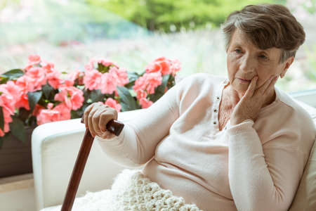 Sad elder woman sitting on white sofa with walking cane in room with pink flowers