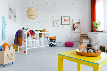 Small balls in copper basket on yellow table in colorful kids room with wooden box and blanket on bed Stock Photo