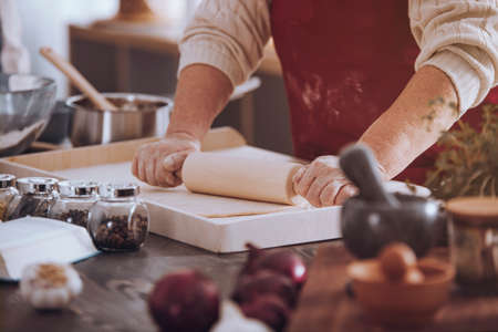 Close-up of senior person rolling out dough on countertop with kitchen tools