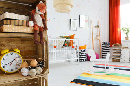 Close-up of plush fox and yellow clock on wooden shelf in colorful childs room with rocking horse Stock Photo