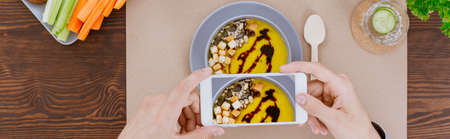 Top view of person photographing hipster vegan food on rustic table with white smartphone Banco de Imagens